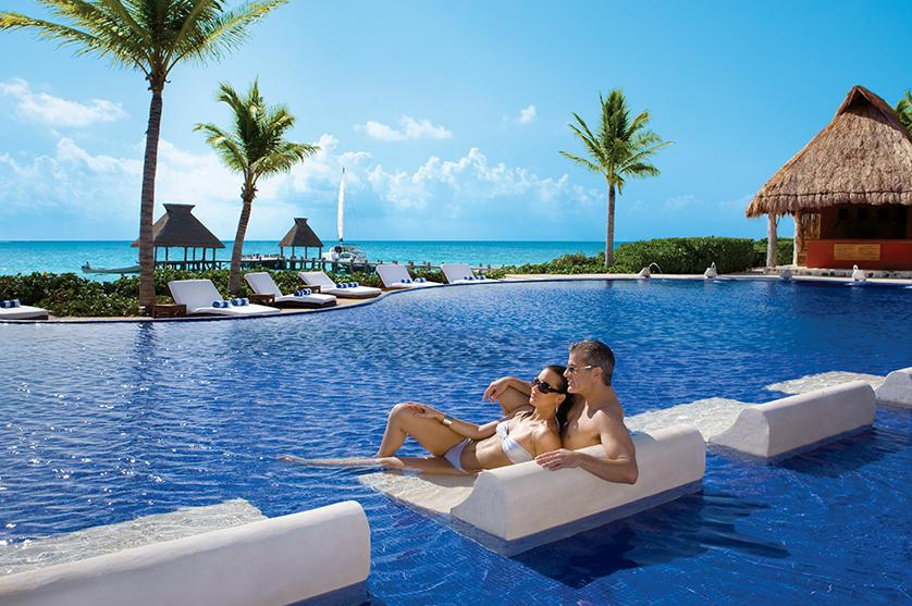 Couple lounging on in-pool chaise lounge overlooking ocean